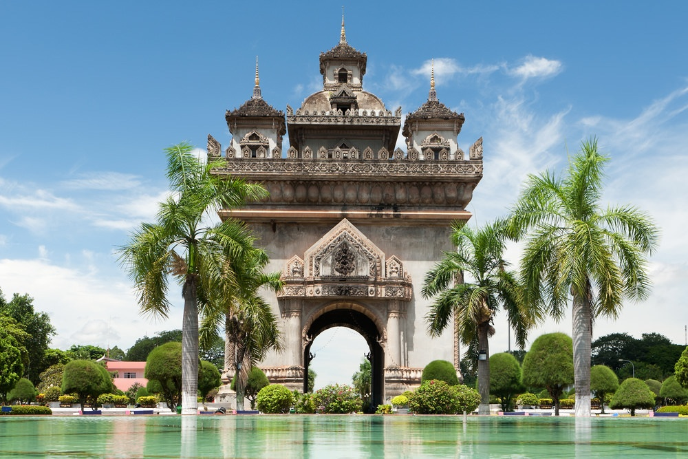 Patuxai Victory Monument with beautiful water and palm trees surrounding.