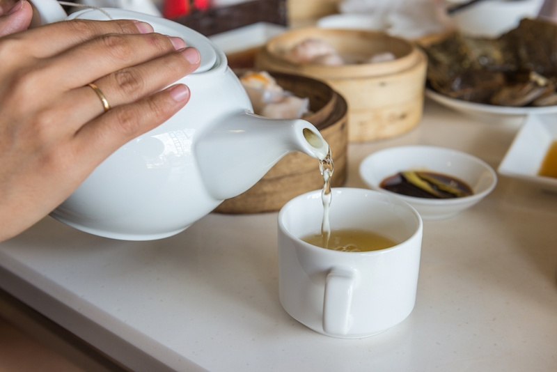 Pouring green tea from white teapot into a cup, dim sum etiquette and tips